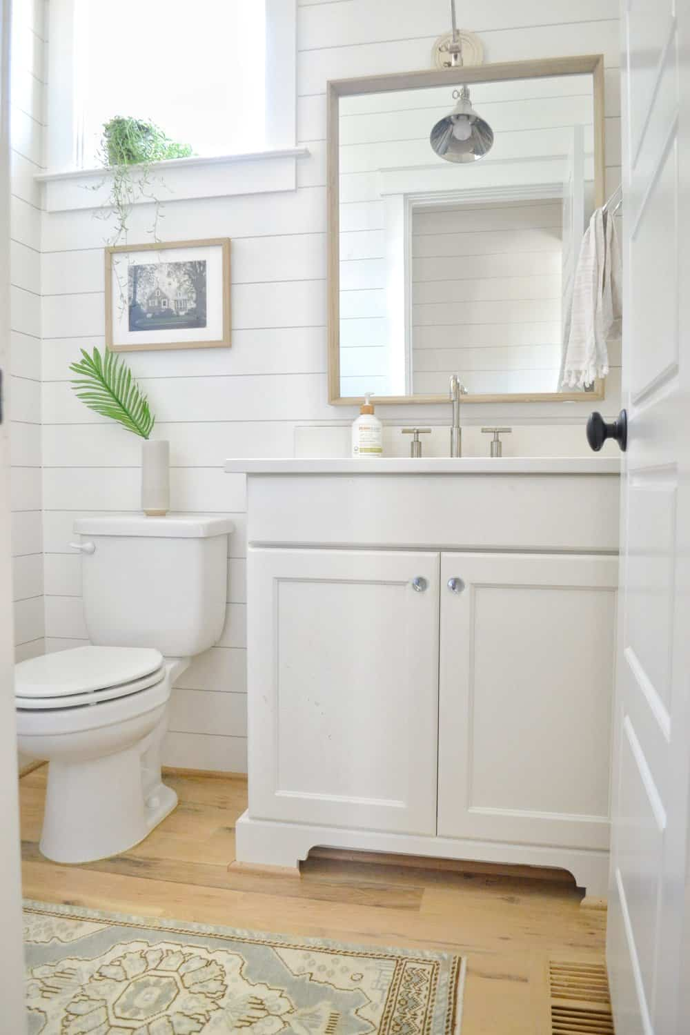 bathroom with shiplap walls and coastal mirror