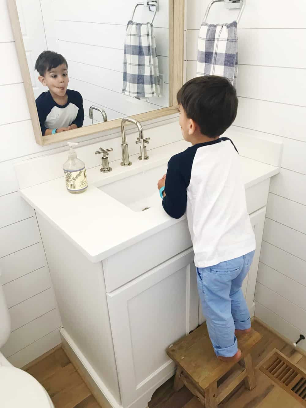 boy in a bathroom making a face in a mirror with shiplap