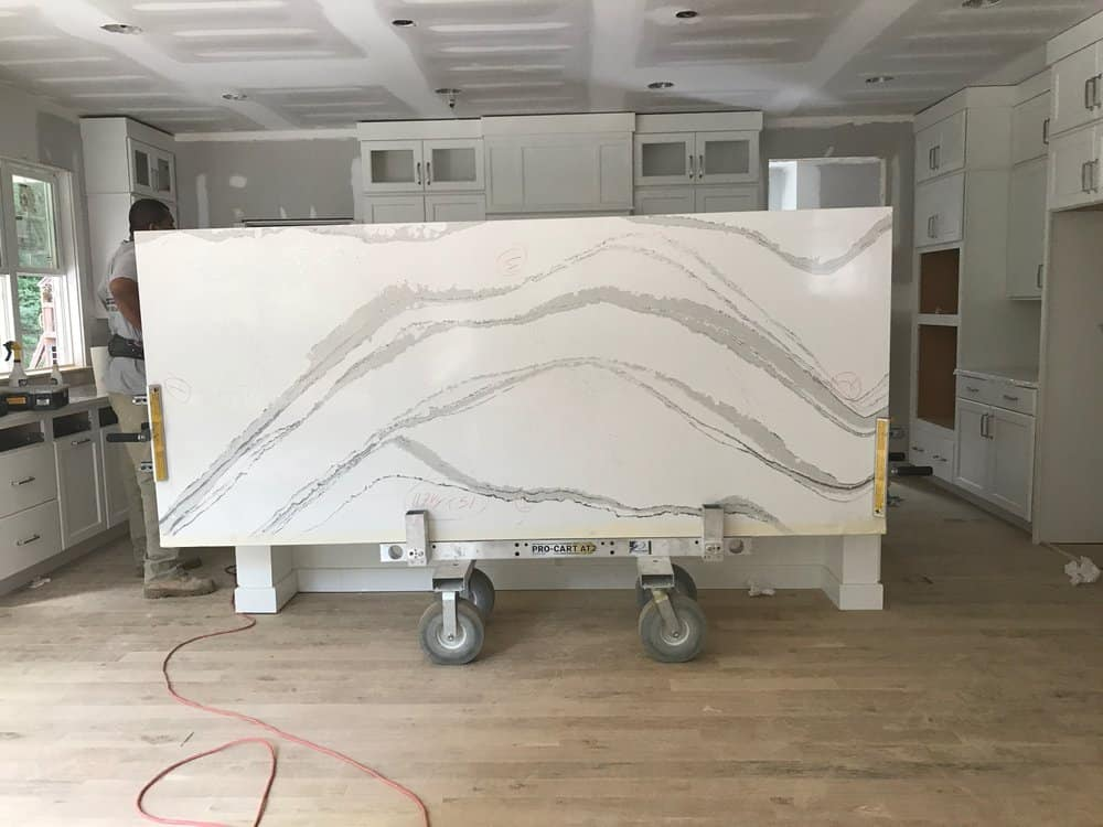 a huge slab of countertop being installed in a new construction kitchen