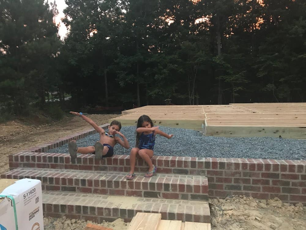 2 kids on the foundation of a new home