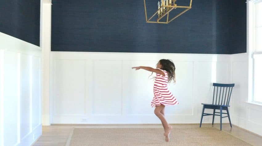girl dancing in a dining room with navy grasscloth wallpaper