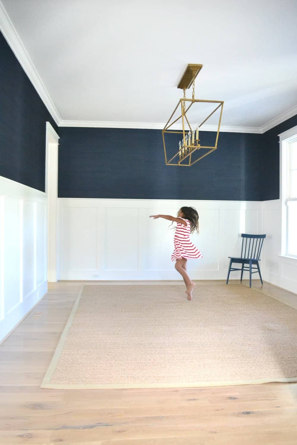 girl dancing in the middle of an empty dining room with navy grasscloth wallpaper