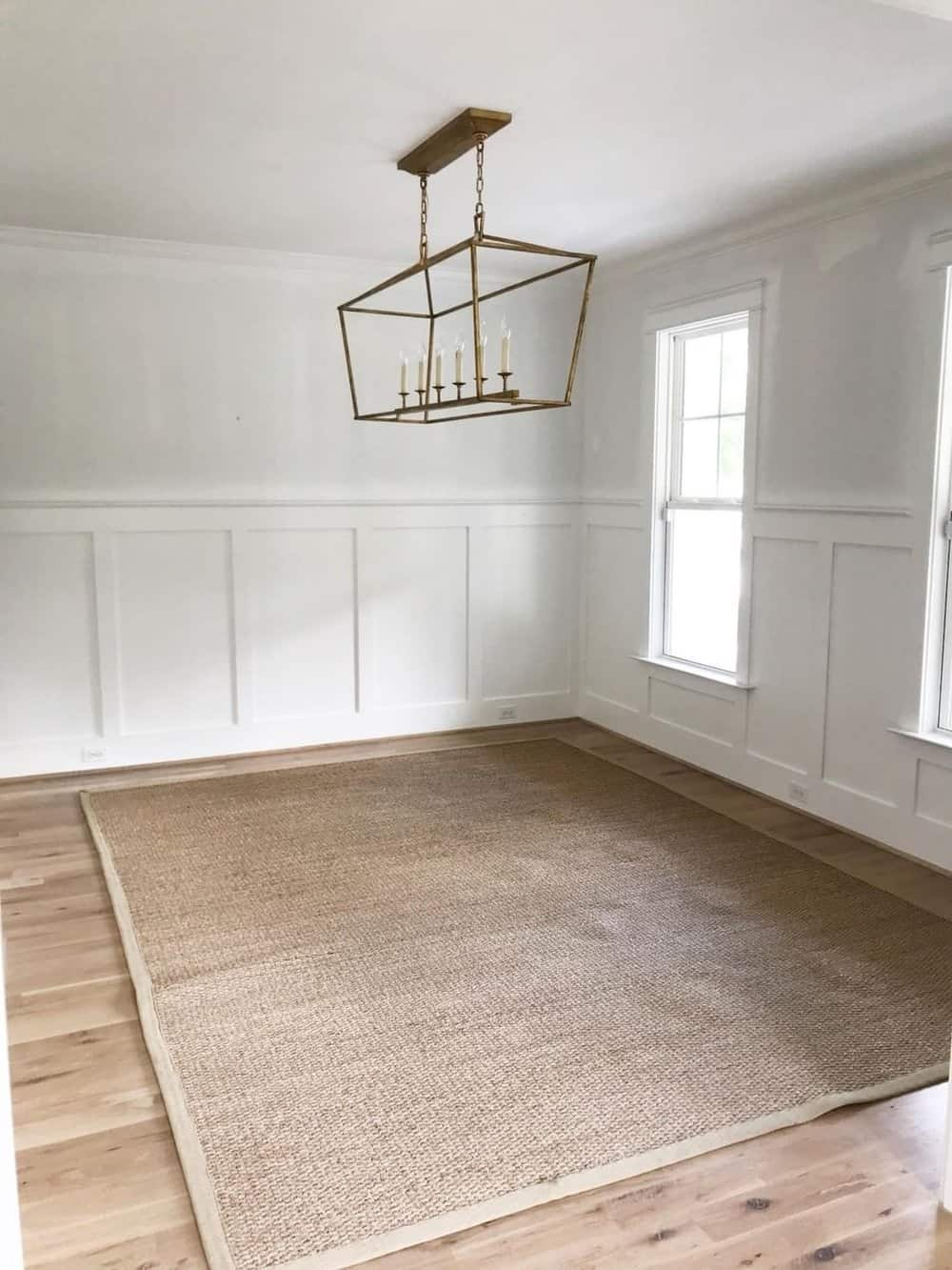empty dining room with white walls and 1 brass pendant and a rug