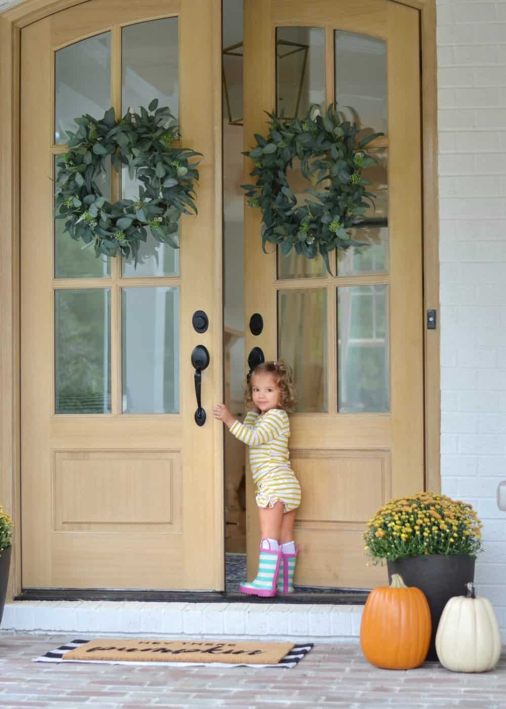 double doors little girls opening on her fall front porch