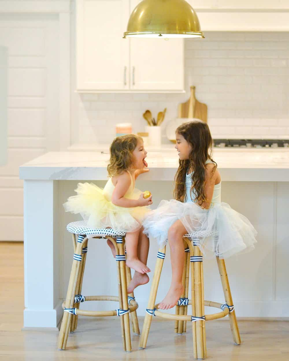2 girls in tutus sitting on Serena & lily bar stools in a kitchen (the riviera)