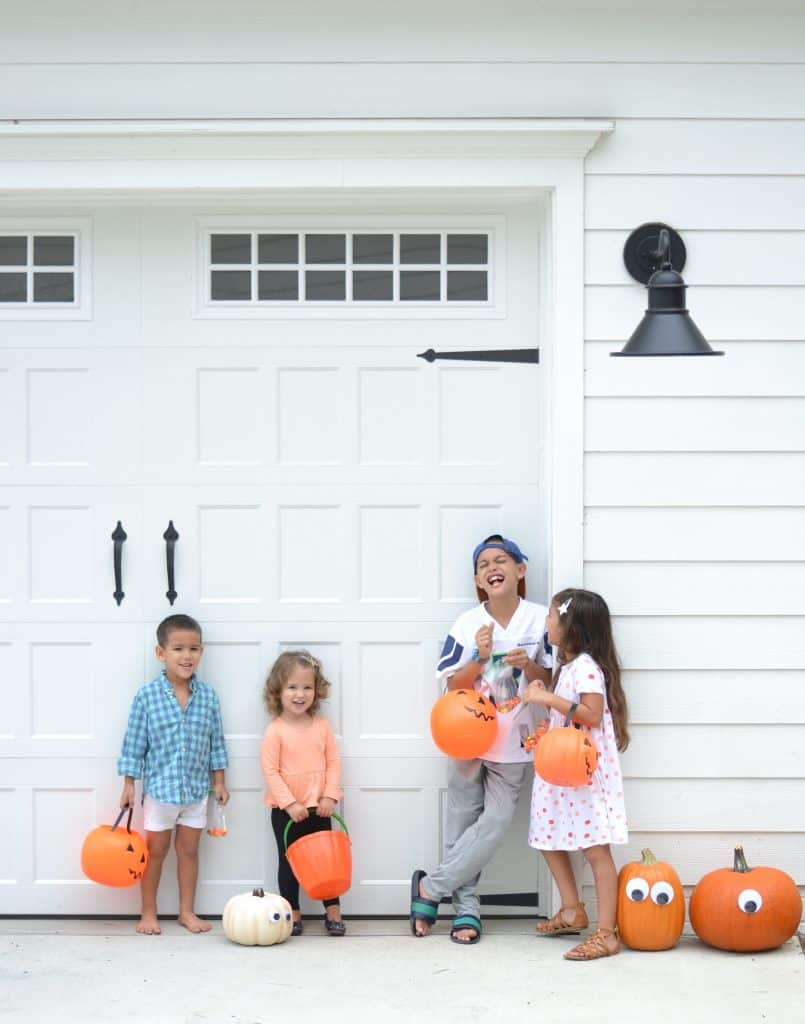 kids outside with eyes on pumpkins- another idea on how to decorate without spending a lot of money