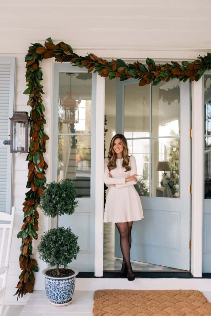 girl in dress on porch in front of faux Christmas Garland
