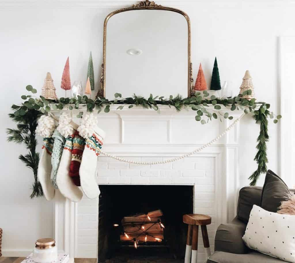 mantle with big garland, little Christmas trees and a gold mirror