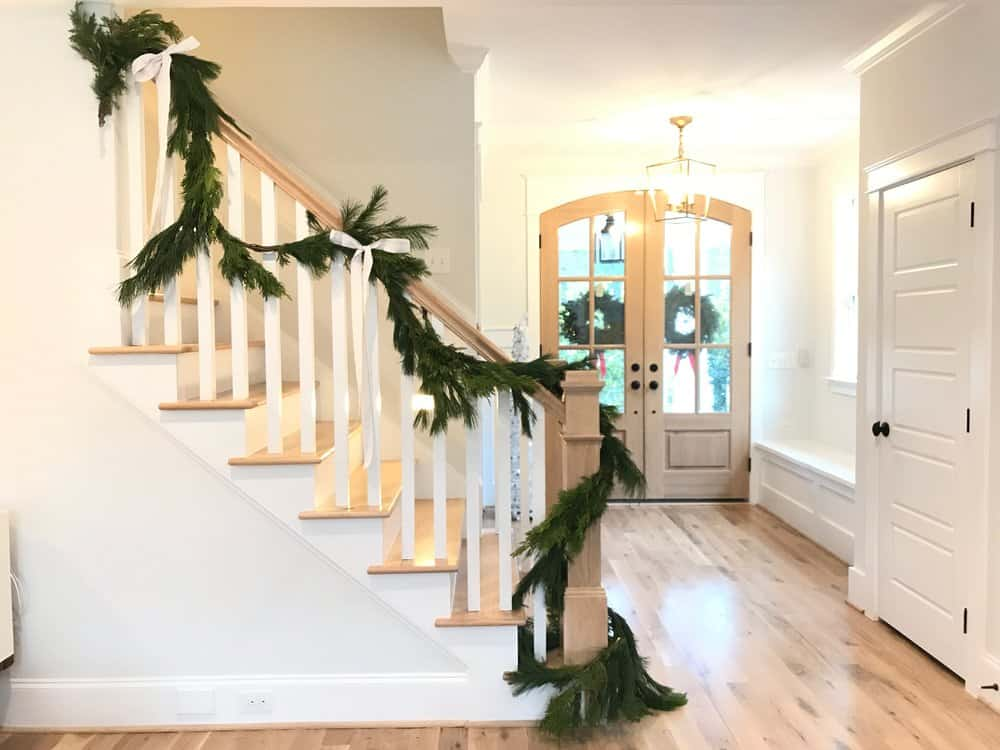 stairs with a real garland and Christmas ribbon tied to it