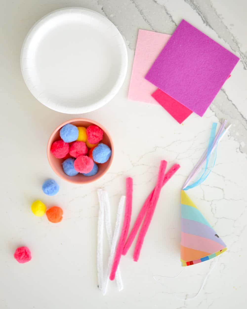 colorful craft supplies laid out for an easter bunny mask