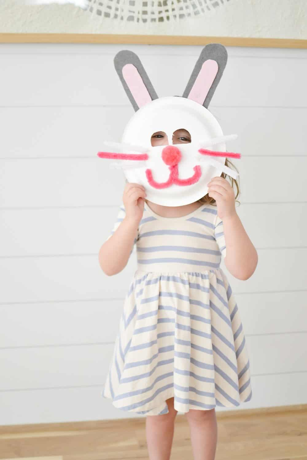 toddler in a dress with an easter bunny mask made out of a paper plate