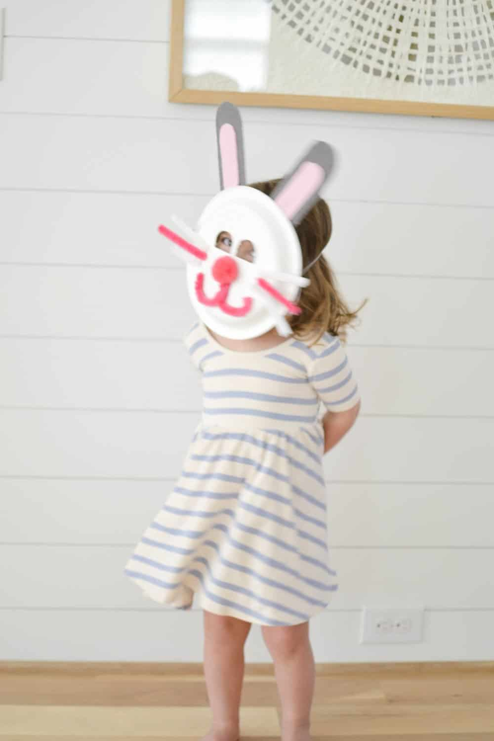 a little girl wearing an easter bunny mask