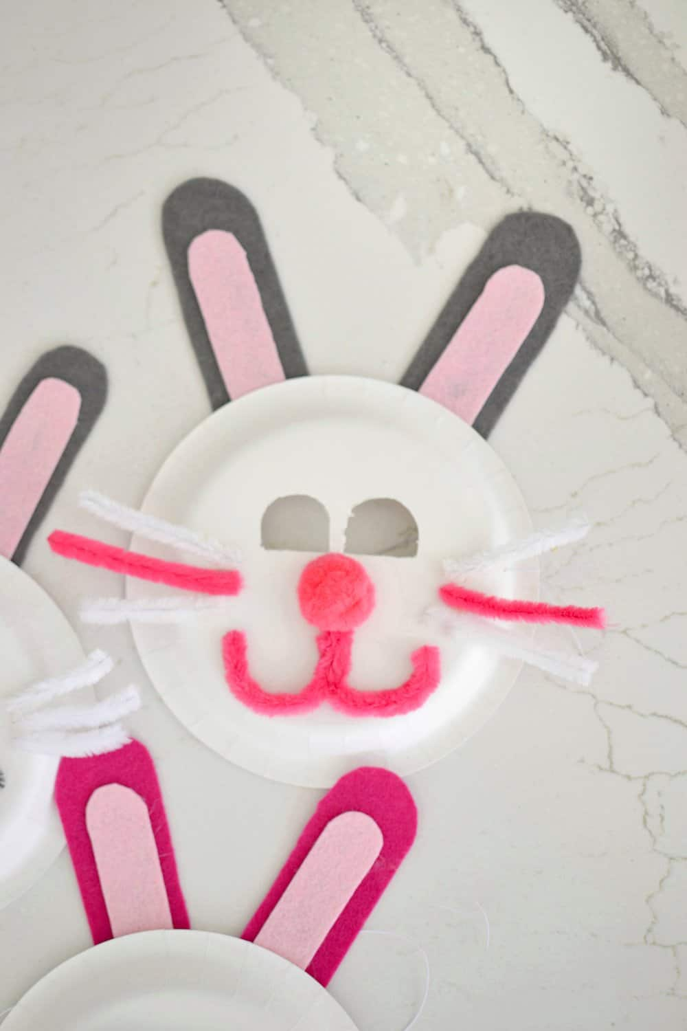 1 pink and white easter bunny mask made out of a paper plate