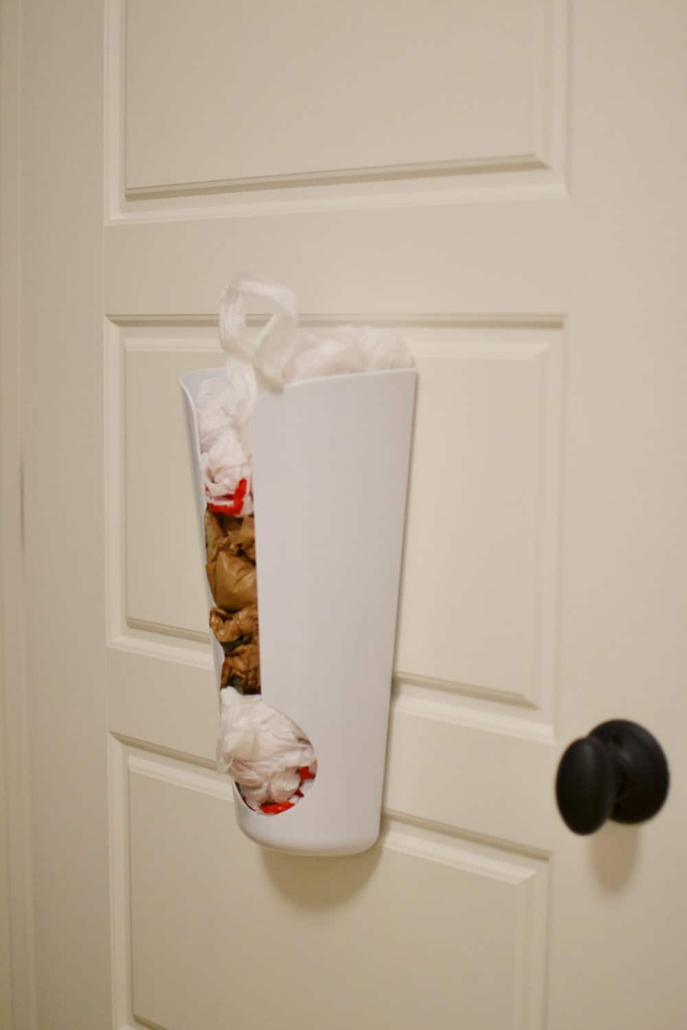 a bag collector on the inside of a walk in pantry