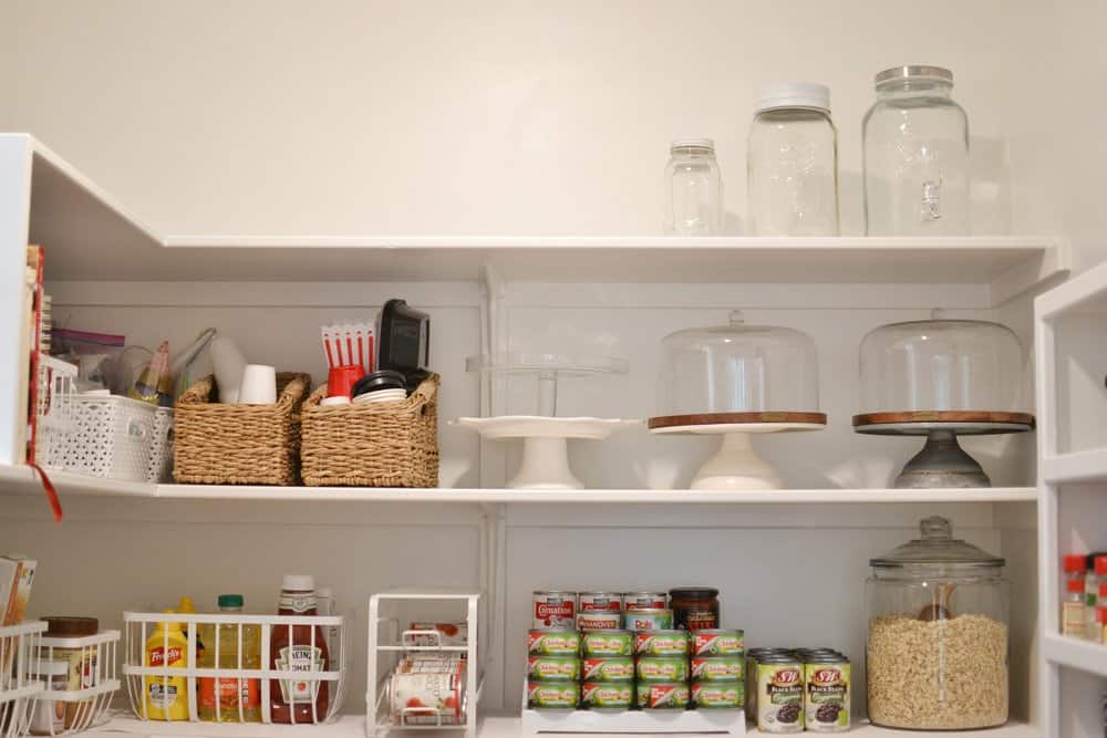 the inside of an organized walk in pantry with canned food stacked up