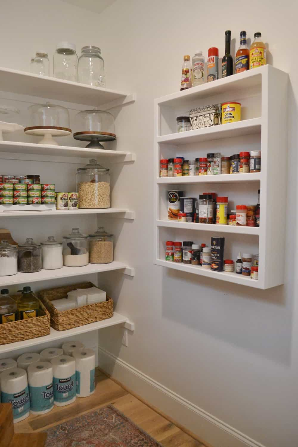 a walk-in pantry with a built in spice rack showing pantry organization