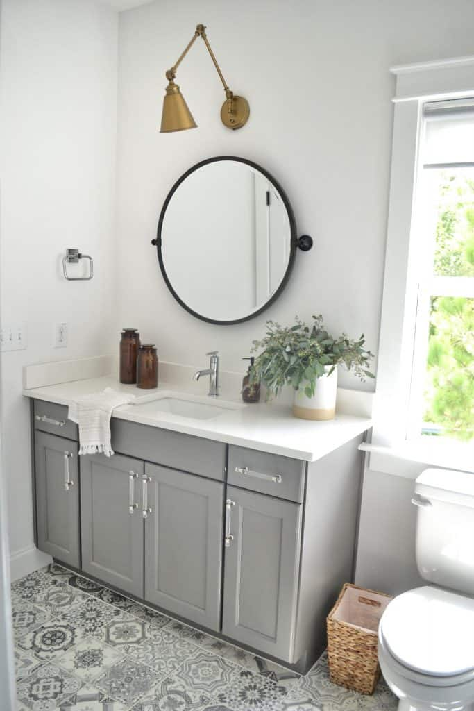 mixing metals with a brass light and black mirror in a bathroom.