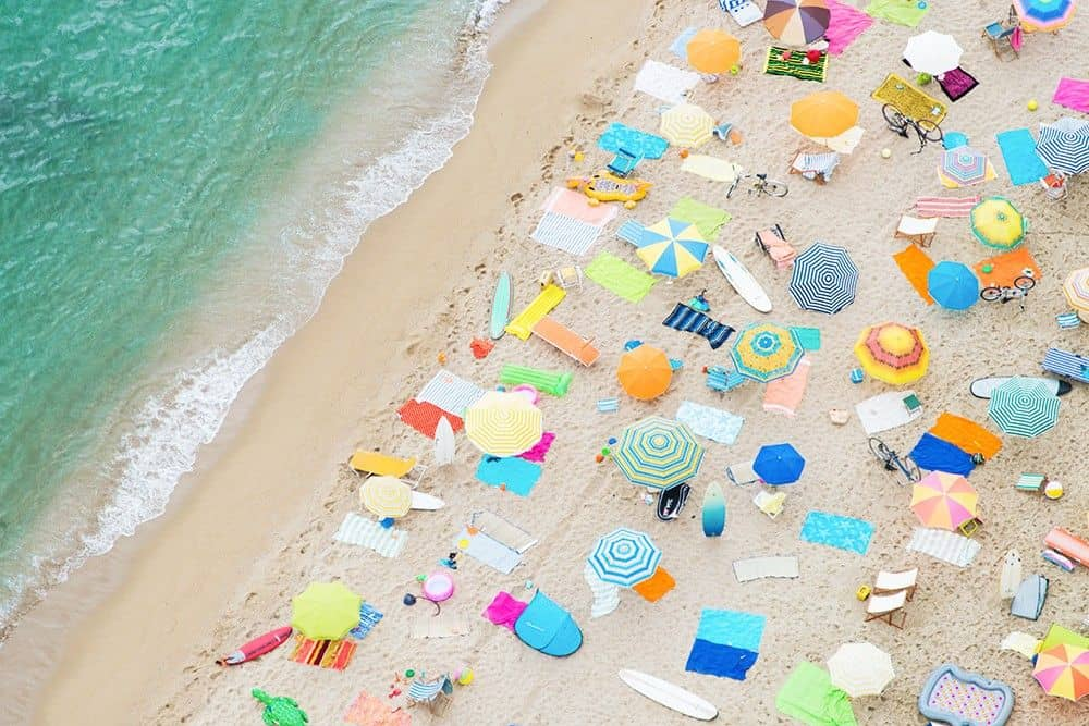 print of a beach from above with umbrellas and towels on the sand