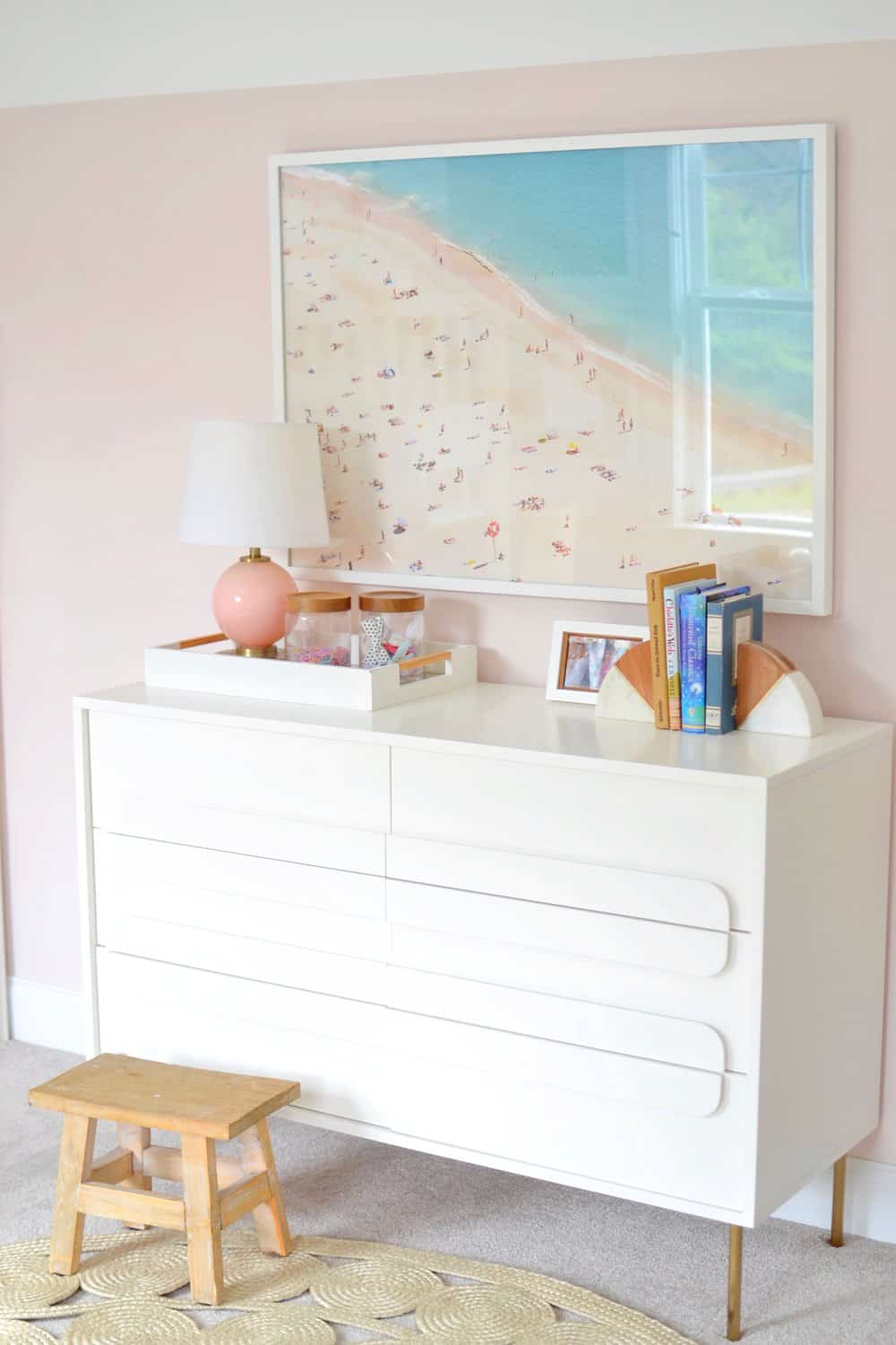 aerial beach photography above a white dresser in a bedroom