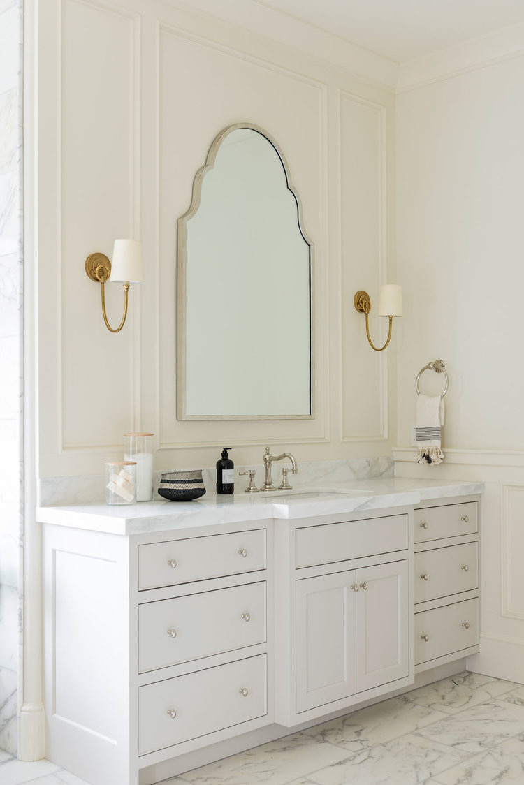 nickel mirror with brass lighting in a bathroom