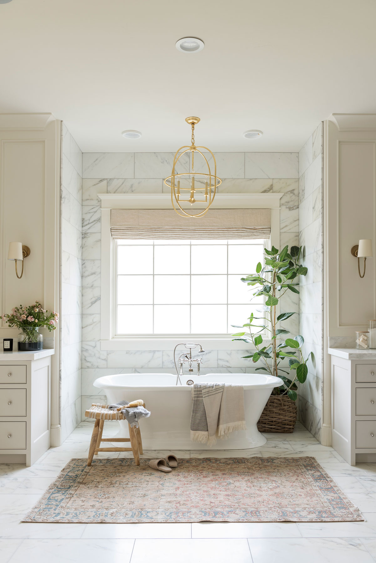 standalone bath tub with nickel faucet and brass lighting