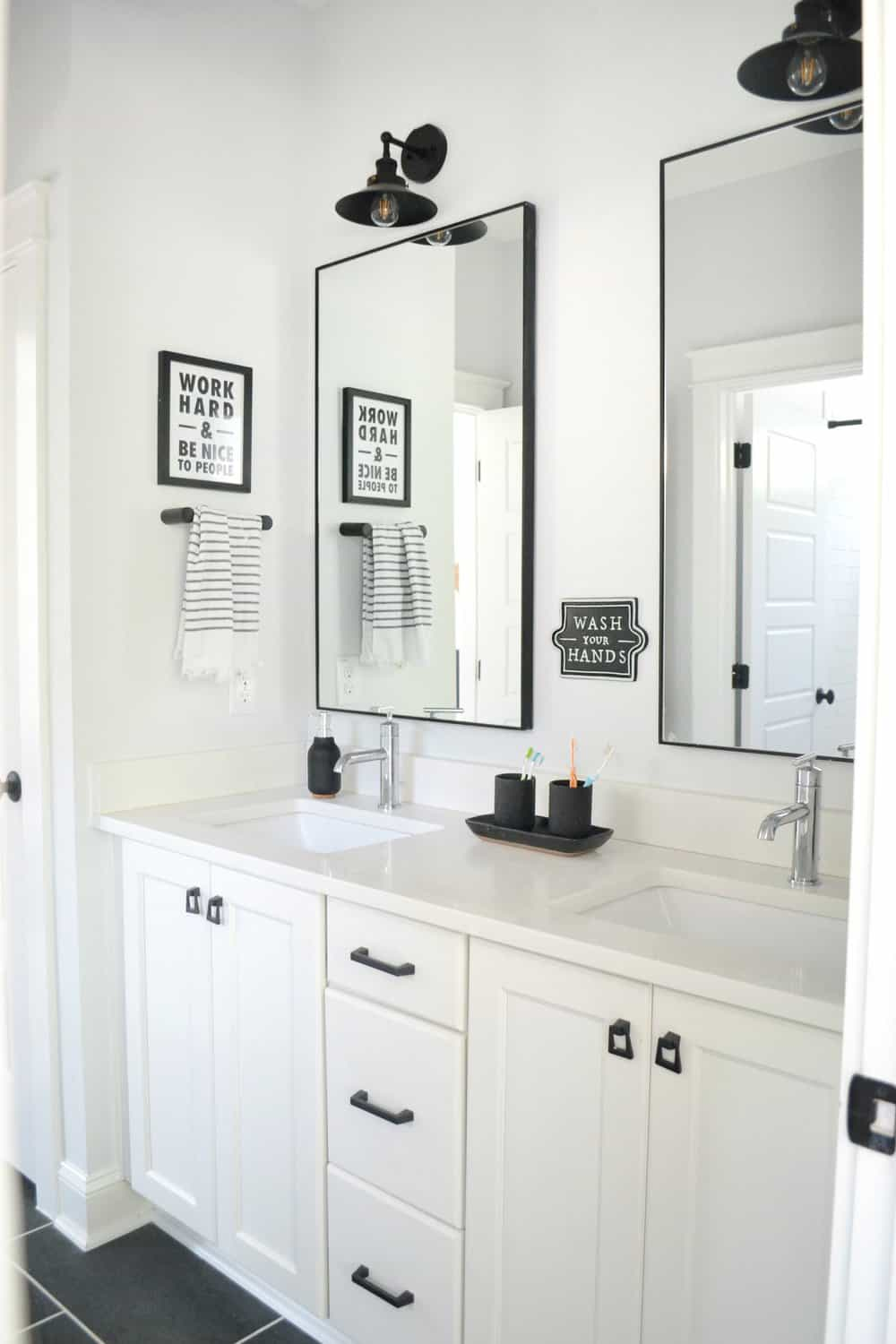 double white vanity with two black mirrors