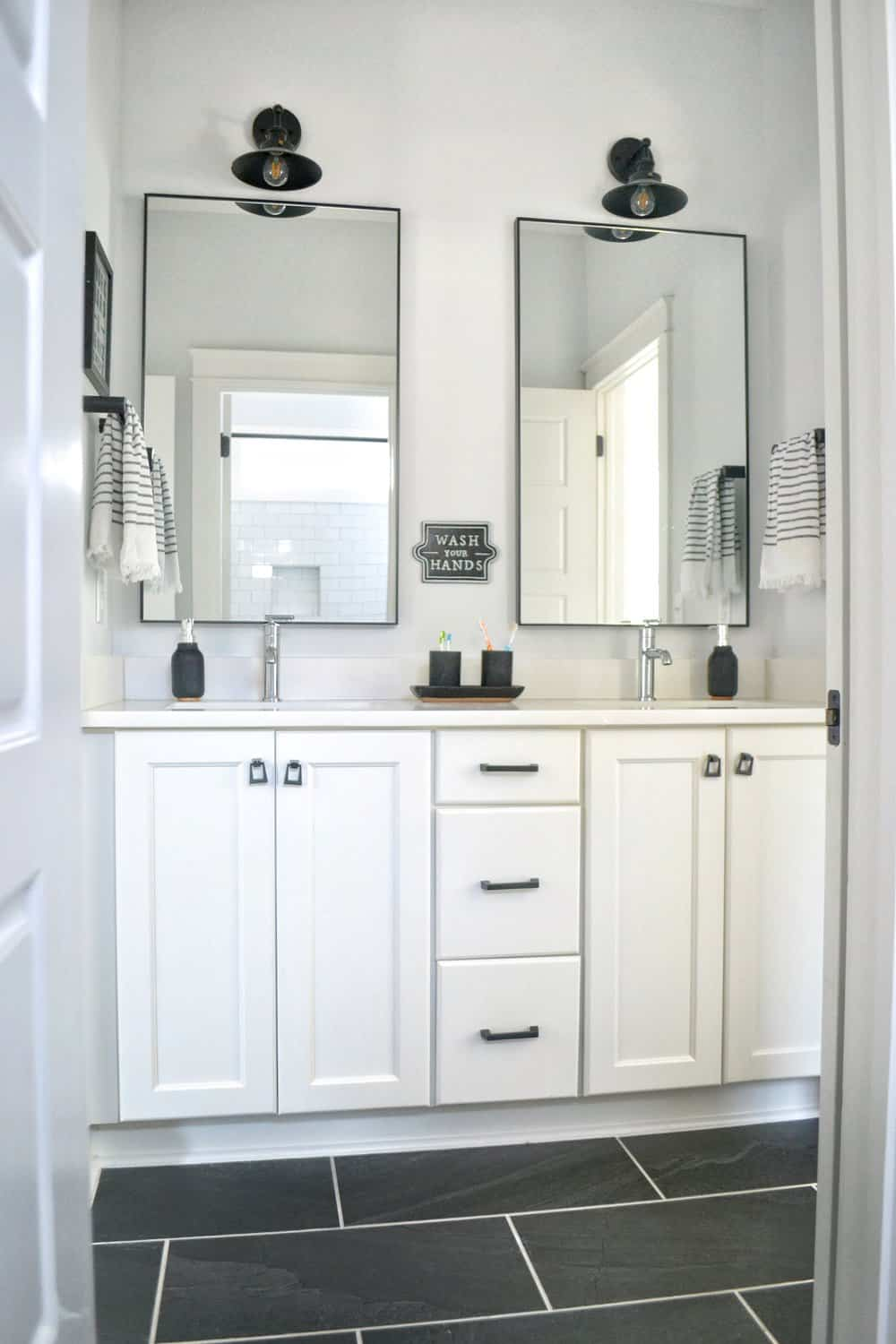 white double vanity with black mirrors in a shared bathroom