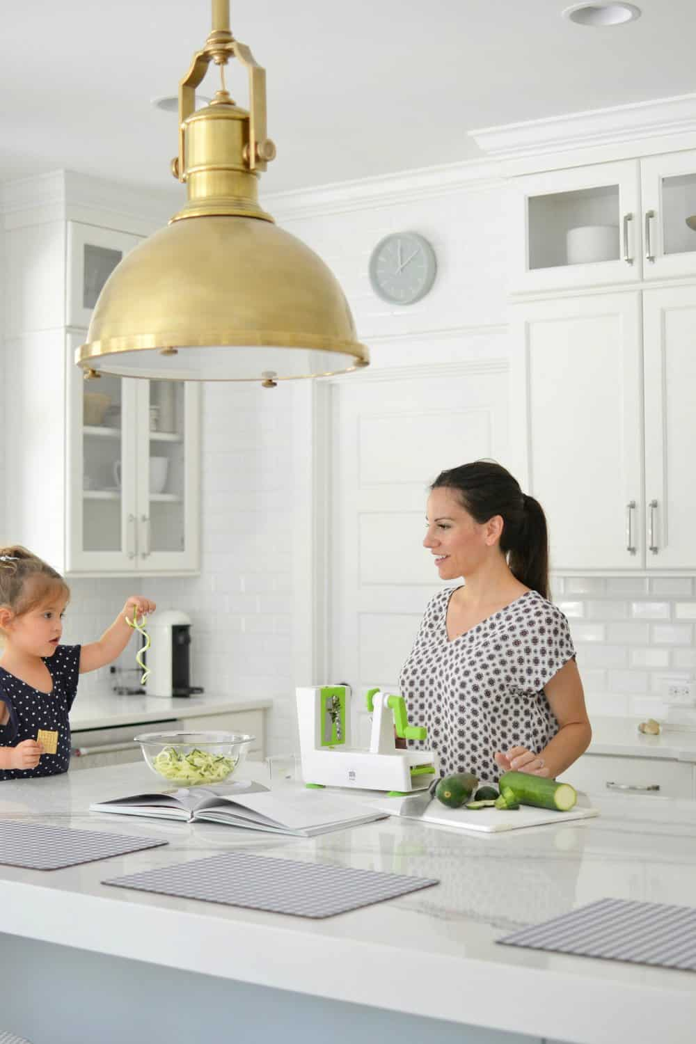 girl holding up noodles in kitchen