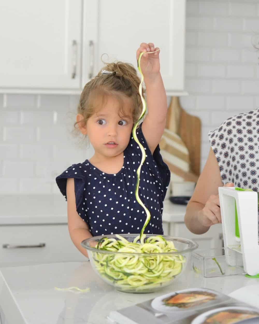 child holding noodles up in a kitchen