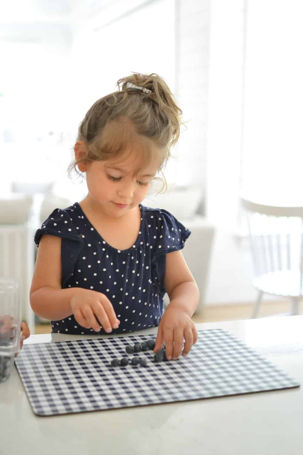 girl counting blueberries on a placemat form Home Centric