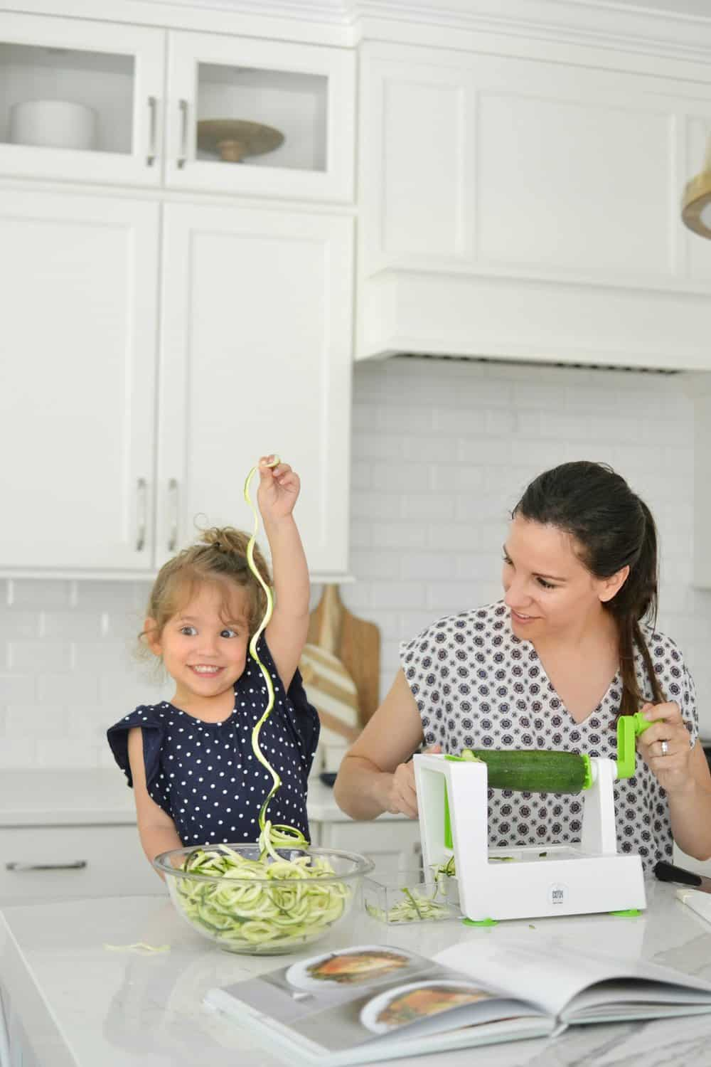 child holding up noodles in kitchen with mother making zoodles