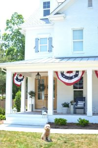 white brick house with patriotic flags