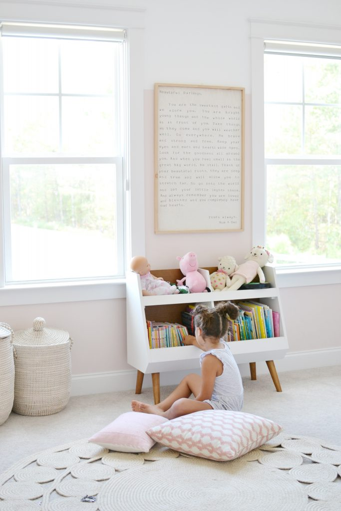 little girl picking a book off a bookshelf in her room