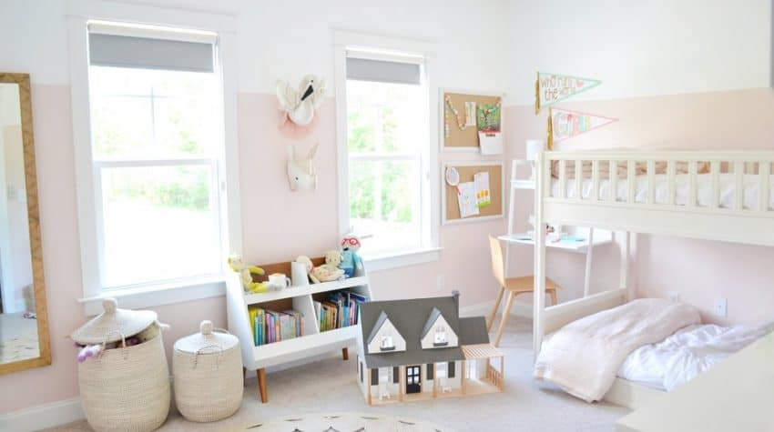 a little girls room with 2 windows and pink walls