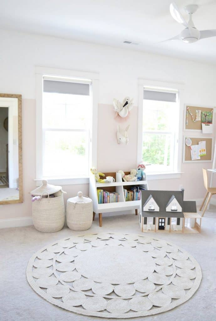 a little girls room with 2 windows and round rug and bunk bed