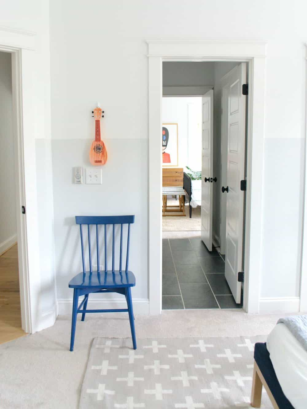 chair and child's guitar in bedroom with walls two tone