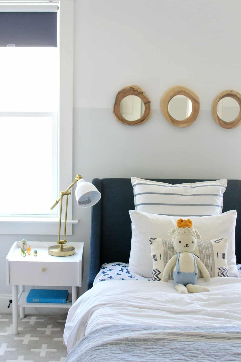 3 mirror above the bed with walls painted two tone, half gray half white