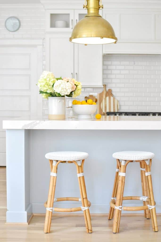 a kitchen island painted Sherwin Williams krypton with gray stools