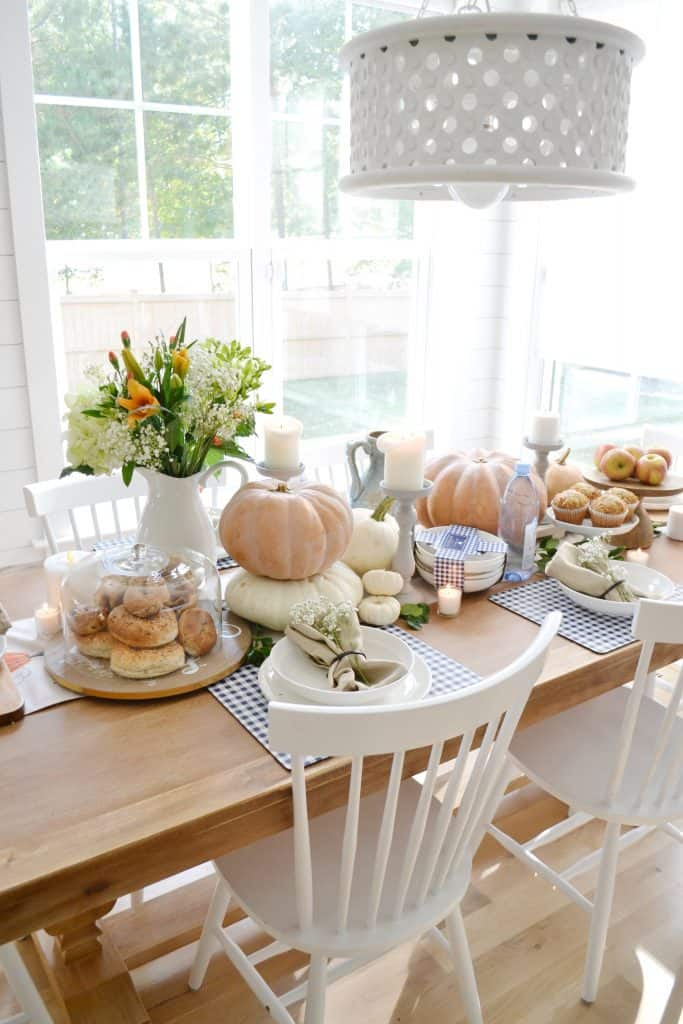 a pumpkin tablescape for fall entertaining with white chairs around a table