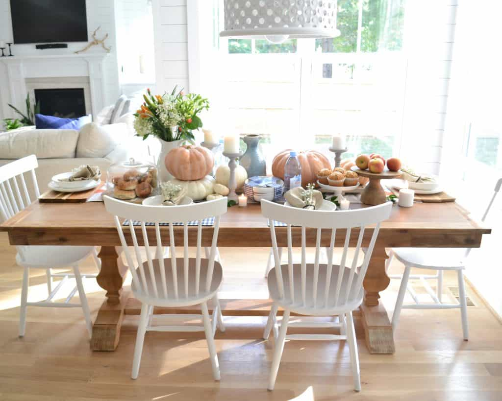 long table covered in pumpkins and food and home decor