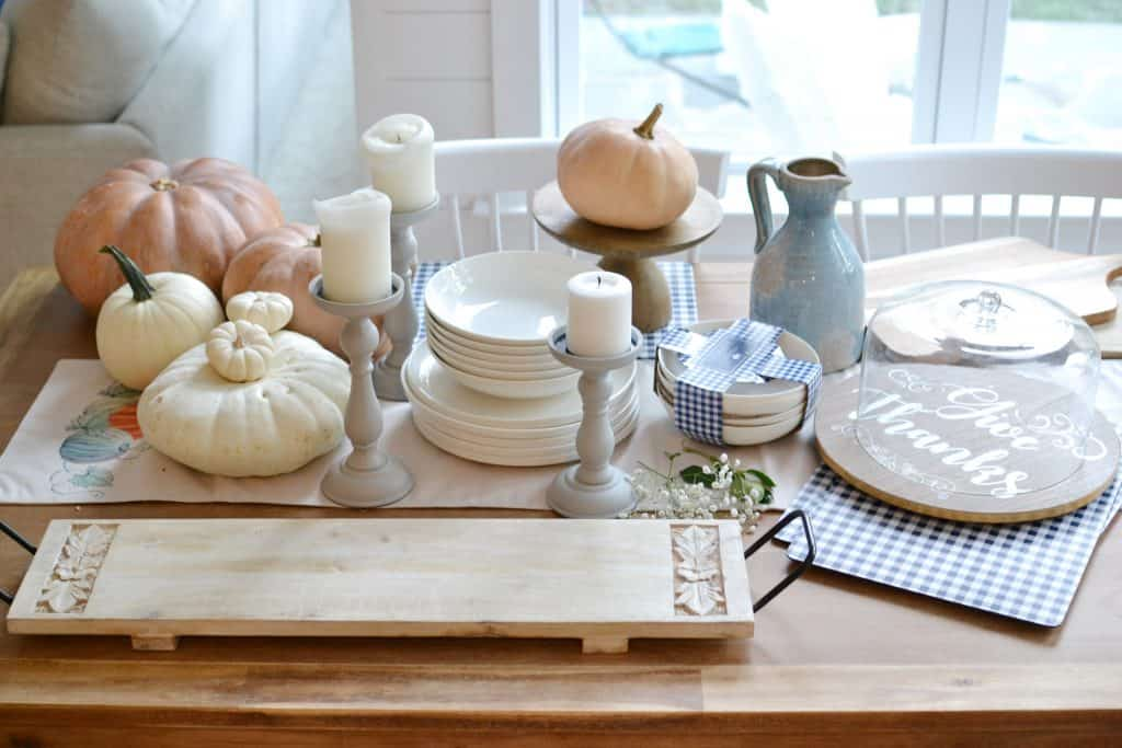 a collection of items from home centric sitting on a table with pumpkins