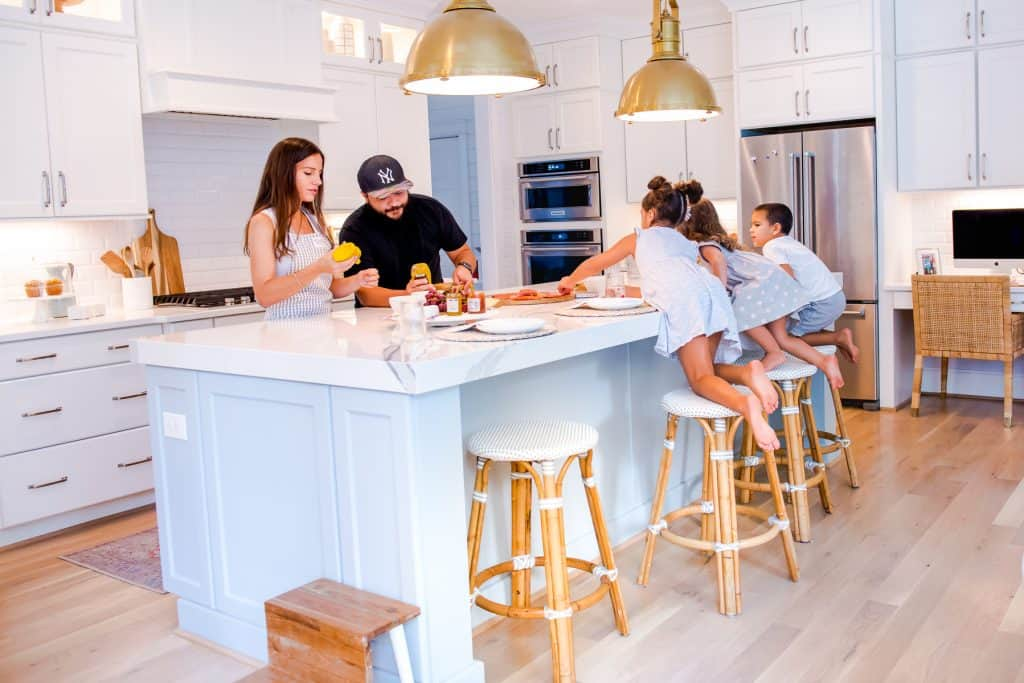 family cooking together at kitchen, 3 kids sitting on kid friendly counter stools