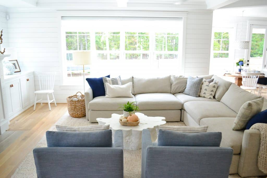 coastal living room design with sectional and blue chairs