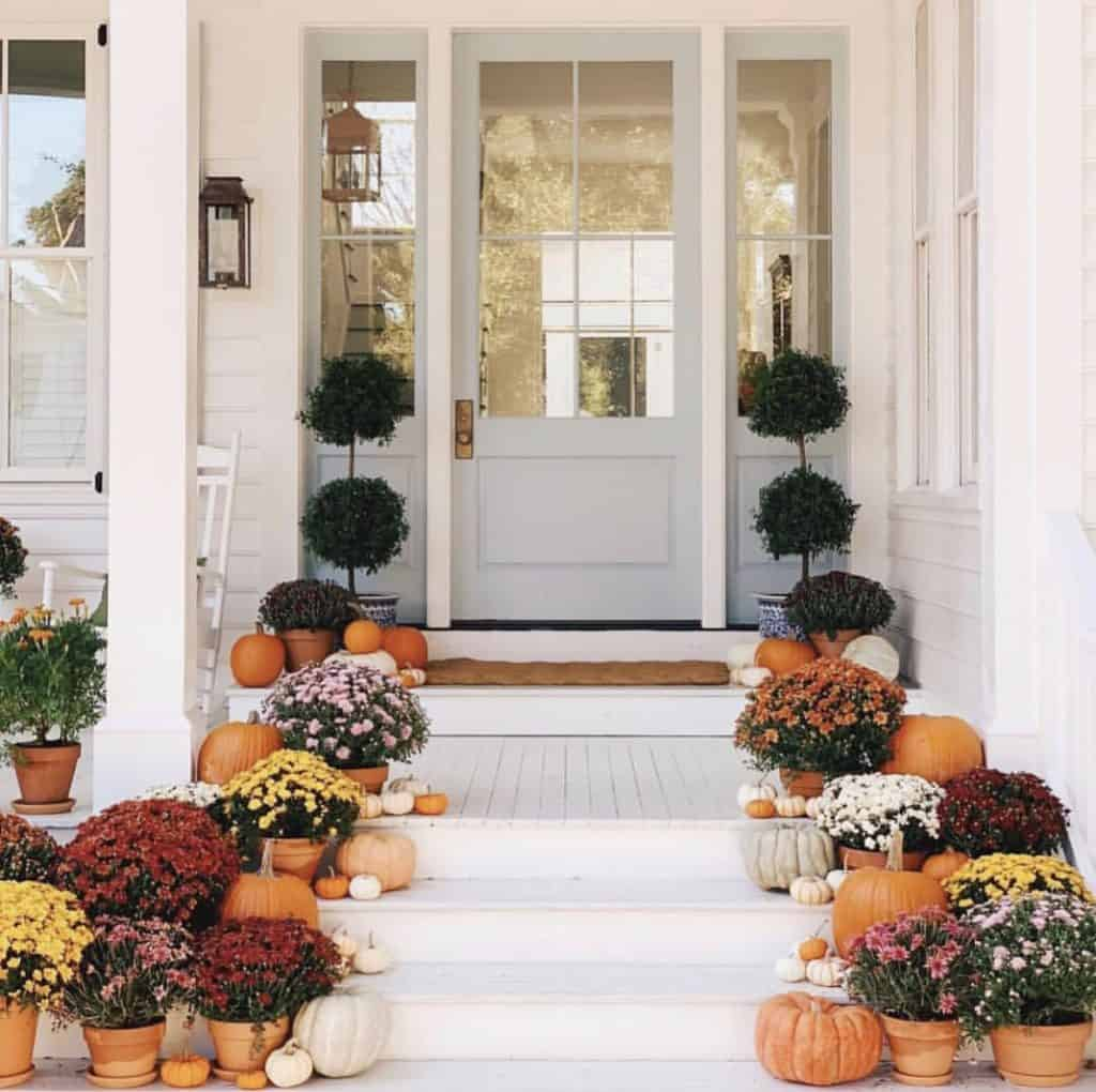 beautiful fall porch on instagram with mums and an aqua door