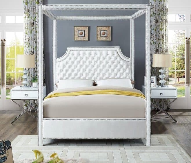 big white canopy bed with upholstered tufting in a bedroom