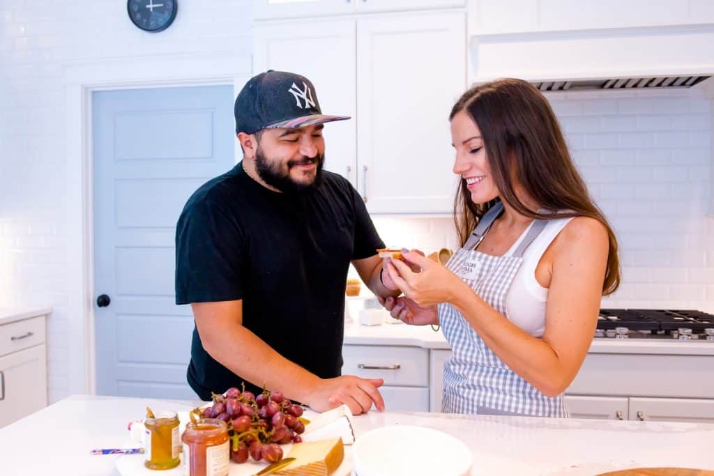 man and woman making a plate of food in kitchen