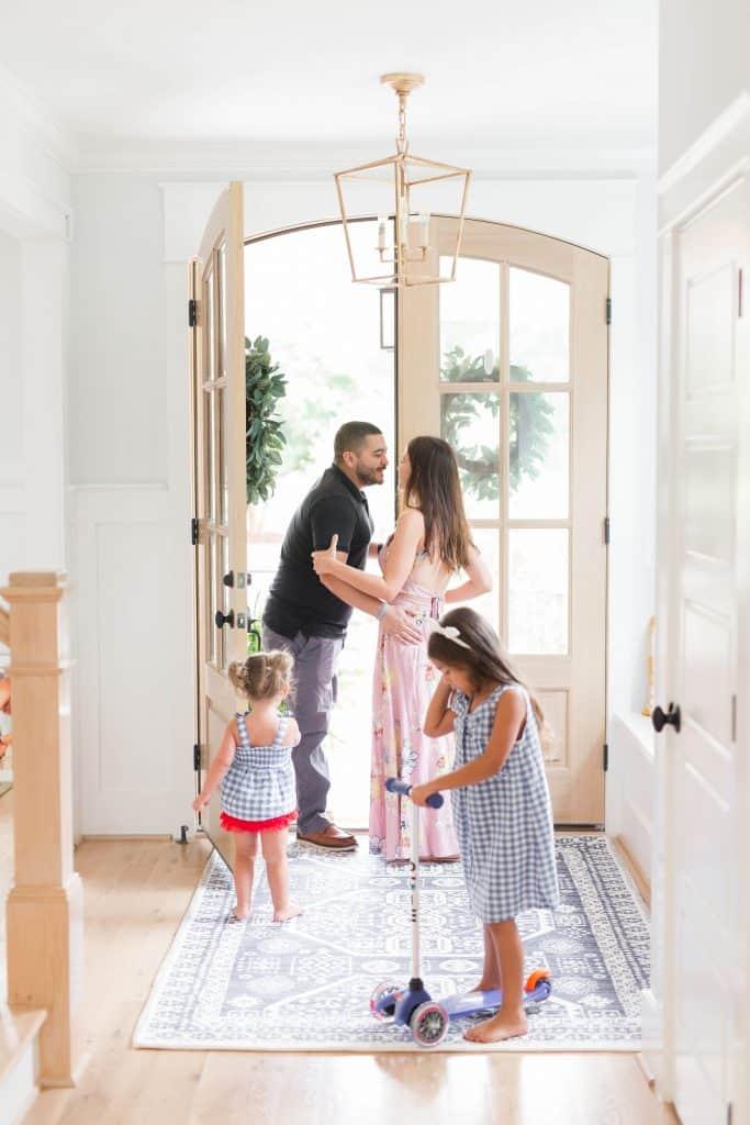 wife kissing husband goodbye in a house