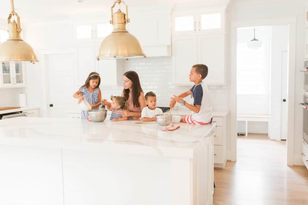 kids cooking in an all white kitchen