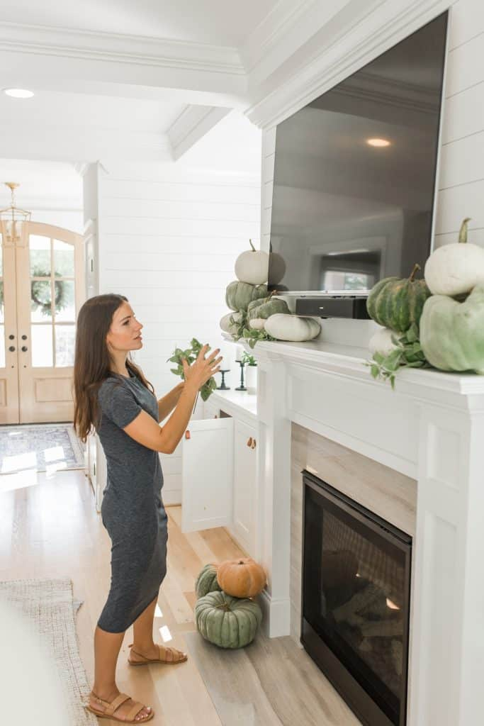 woman decorating her fireplace mantel with tv