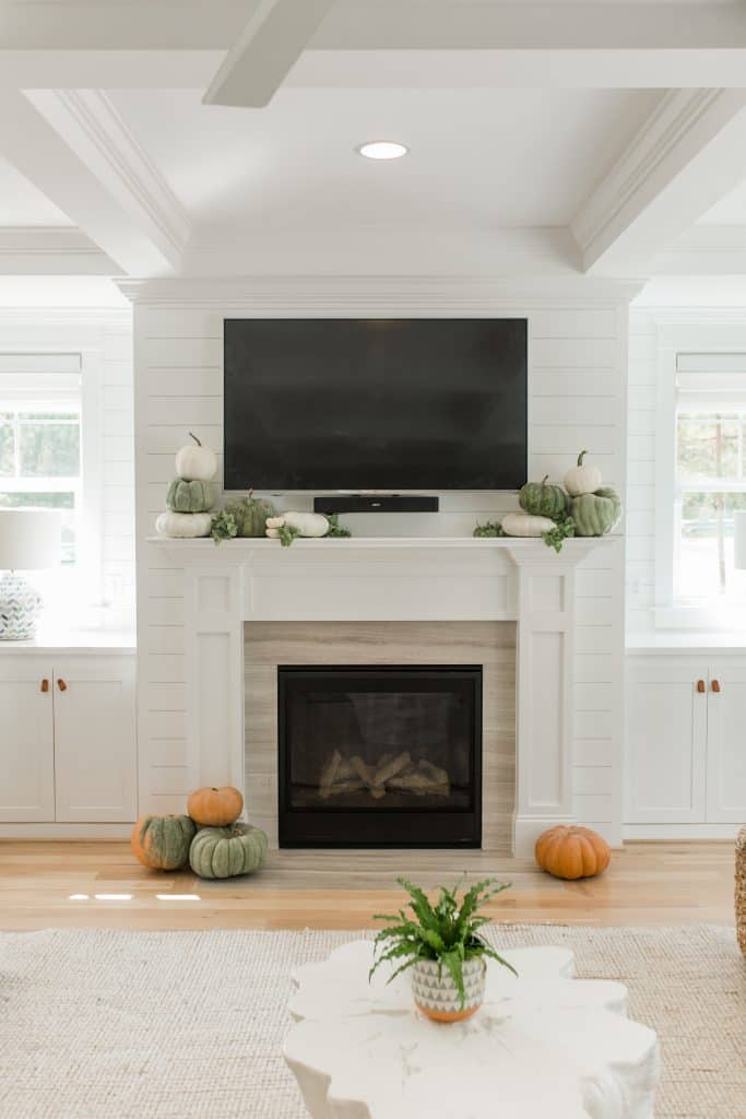 mantel decor with tv and green pumpkins on the mantel